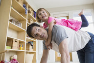 Father carrying daughter on back in living room - HEROF04599