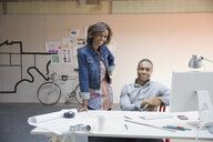 Portrait of confident business people at desk in office - HEROF04605