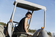 Mid adult woman on tractor in Sweden - FOLF09702