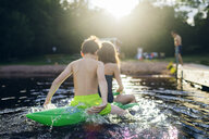 Brother and sister on a pool toy in a lake in Kappemalagol, Sweden - FOLF09762