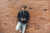 Teenage boy leaning on a brick wall looks at his phone in Sweden - FOLF09894