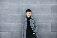 Portrait of stylish young man wearing black turtleneck pullover and grey coat - JRFF02452