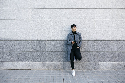 Young man with mobile phone leaning against wall waiting - JRFF02461