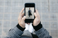 Man holding smartphone with photo of himself, close-up - JRFF02464