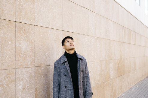 Young man wearing turtleneck pullover and grey coat looking up - JRFF02473