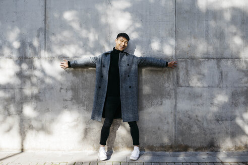 Laughing young man wearing turtleneck pullover and grey coat standing in front of concrete wall - JRFF02476