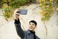 Portrait of young man taking selfie with smartphone - JRFF02479