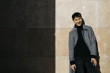 Portrait of fashionable young man wearing black turtleneck pullover and grey coat - JRFF02482