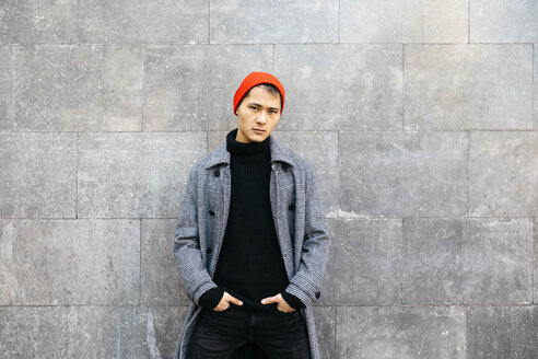 Portrait of stylish young man wearing cap, black turtleneck pullover and grey coat - JRFF02485