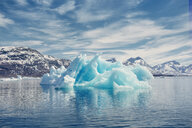 View of icebergs melting in sea by mountains against cloudy sky - ASTF01943