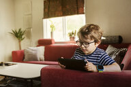 Boy playing on a tablet in a living room in Sweden - FOLF10045