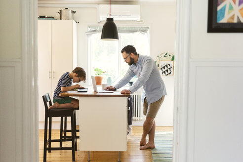 Mid adult man and boy use devices in a domestic kitchen in Sweden - FOLF10048