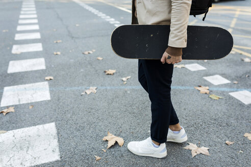 Man with backpack and skateboard crossing the street in autumn, partial view - VABF02091
