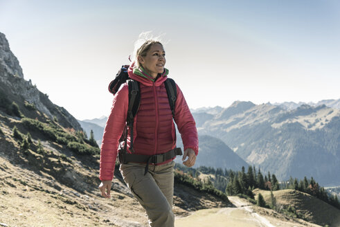 Austria, Tyrol, smiling woman on a hiking trip in the mountains - UUF16339