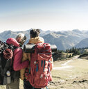 Austria, Tyrol, rear view of couple on a hiking trip in the mountains enjoying the view - UUF16342