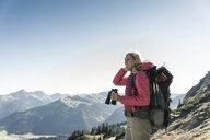 Austria, Tyrol, smiling woman with binoculars on a hiking trip - UUF16345