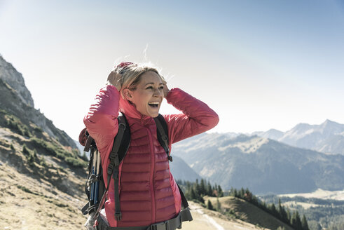 Austria, Tyrol, happy woman on a hiking trip in the mountains enjoying the view - UUF16351