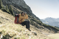 Austria, Tyrol, man having a break during a hiking trip in the mountains looking through binoculars - UUF16354
