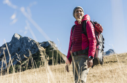 Austria, Tyrol, happy woman on a hiking trip in the mountains - UUF16381