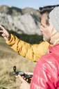 Austria, Tyrol, couple with compass hiking in the mountains - UUF16390
