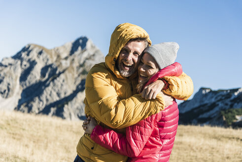 Austria, Tyrol, happy couple hugging on a hiking trip in the mountains - UUF16393