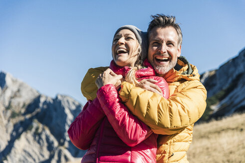 Austria, Tyrol, happy couple hugging on a hiking trip in the mountains - UUF16396
