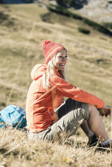 Austria, Tyrol, smiling woman sitting on alpine meadow - UUF16399
