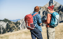 Austria, Tyrol, couple with map hiking in the mountains - UUF16402