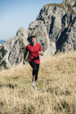 Austria, Tyrol, man running in the mountains - UUF16414