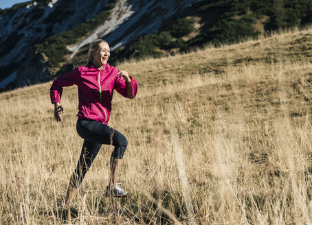 Austria, Tyrol, happy woman running in the mountains - UUF16420