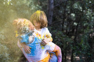 Father carrying son piggyback,  full of colorful powder paint, celebrating Holi, Festival of Colors - ERRF00452