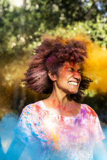 Woman shaking her head, full of colorful powder paint, celebrating Holi, Festival of Colors - ERRF00470