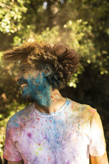 Man shaking his head, full of colorful powder paint, celebrating Holi, Festival of Colors - ERRF00476