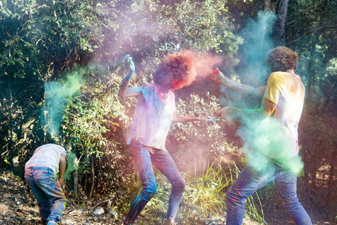 happy family celebrating Holi festival in the forest, throwing colorful powder paint - ERRF00500