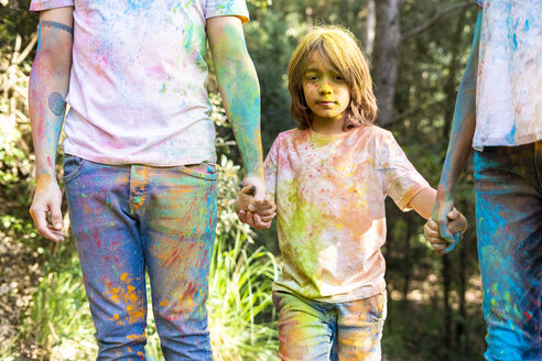 Family in the forest, full of colorful powder paing, after celebrating Holi, Festival of colors - ERRF00506