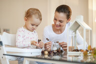 Mother and little daughter tinkering autumnal decorative house at home - DIGF05589