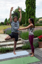 Female yoga teacher teaching young man yoga in garden, tree pose - CUF46586