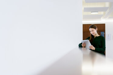 Woman using digital tablet on low wall - CUF46640