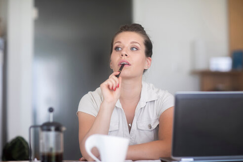Businesswoman thinking in front of laptop - CUF46712