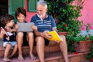 Grandfather sitting with grandsons on front door steps - CUF46814