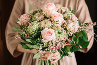 Woman holding bouquet of fresh soft pink roses - CUF46823
