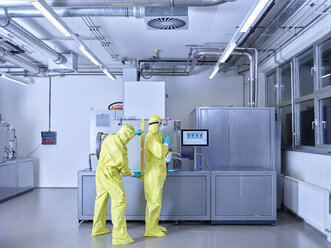 Chemists working in industrial laboratory, wearing protective clothing in the clean room - CVF01093