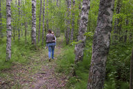 Finland, Kuopio, mother and daughter walking in a birch forest - PSIF00209