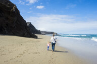 Spain, Canary Islands, Fuerteventura, La Pared, Playa del Viejo Rey, mother and daughter walking on the beach - RUNF00854