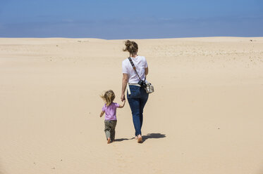 Spain, Canary Islands, Fuerteventura, Parque Natural de Corralejo, mother and daughter walking in sand dunes - RUNF00866