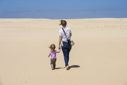 Spain, Canary Islands, Fuerteventura, Parque Natural de Corralejo, mother and daughter walking in sand dunes - RUNF00866