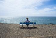 Spain, Canary Islands, Fuerteventura, woman enjoying the sunshine at El Cotillo beach - RUNF00869