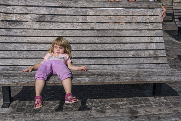 Sweden, girl lying on wooden bench on town square - RUNF00944