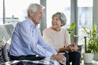 Senior couple sitting on couch talking together - RBF06981