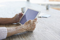 Woman's hands holding digital tablet, close-up - RBF06987